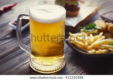 Glass mug of light beer with snacks on dark wooden table. Retro stylization - stock photo