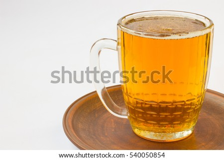 Glass mug with beer on a ceramic plate. White background