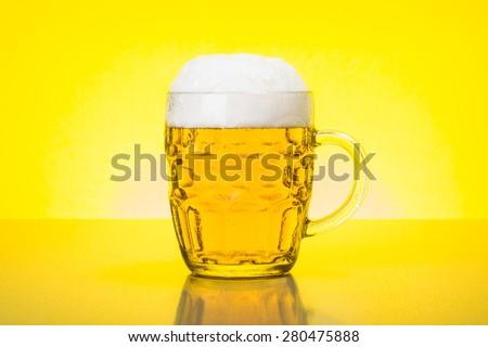 Glass mug with fresh, foamy beer on backlit yellow background - stock photo