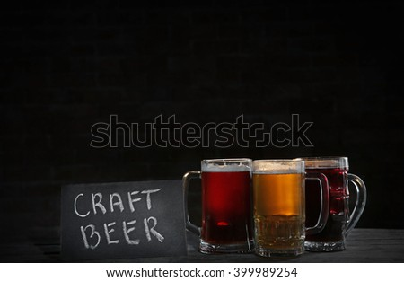 Glass mugs with different sorts of craft beer on dark background - stock photo
