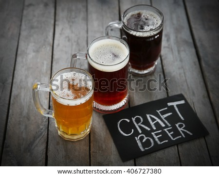 Glass mugs with different sorts of craft beer on wooden table - stock photo