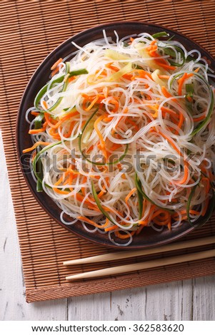 Glass noodle salad with cucumber and carrot on a plate close-up. Vertical top view