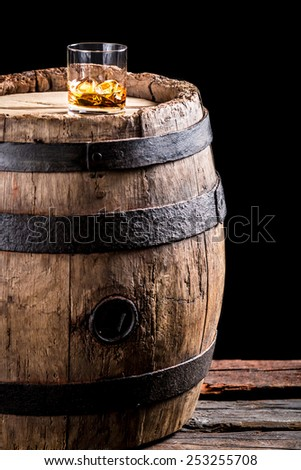 Glass of aged brandy or whiskey on the rocks and old oak barrel - stock photo