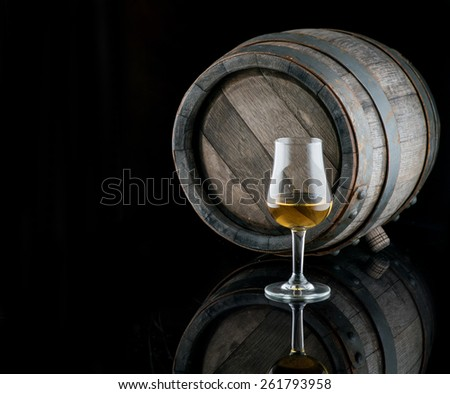 Glass of alcohol on a background of oak  - stock photo