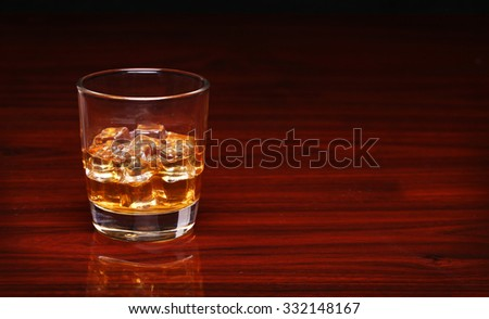 Glass of alcohol scotch whiskey with ice cube on wooden table and black background