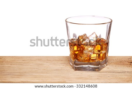 Glass of alcohol scotch whiskey with ice cube on wooden table and white background