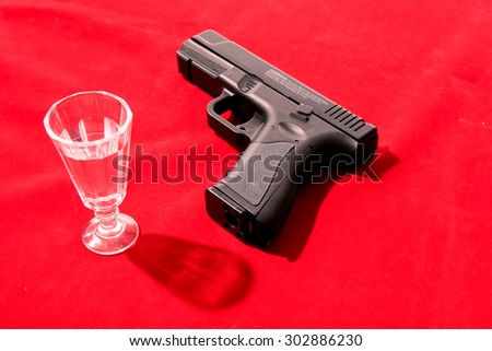 Glass of alcoholic drink and gun on red background - stock photo