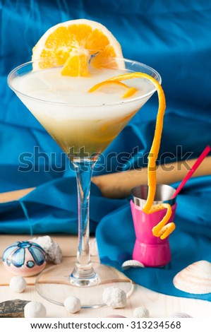 glass of alcoholic drink cocktail with orange slices and cubes on blue
