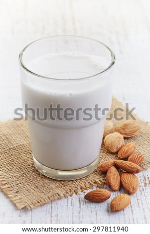 Glass of almond milk  on white wooden background