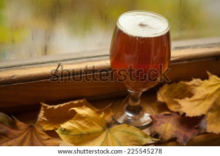 Glass of amber beer standing on windowsill with autumn leaves and a fogged window in the background - stock photo