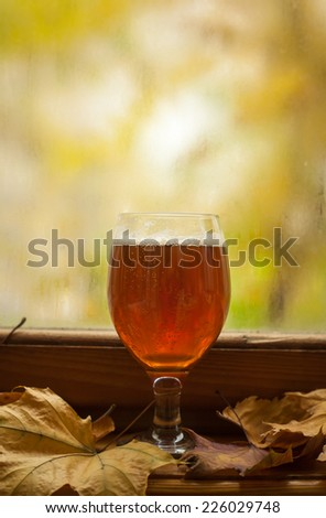 Glass of amber beer standing on windowsill with autumn leaves and a fogged window in the background