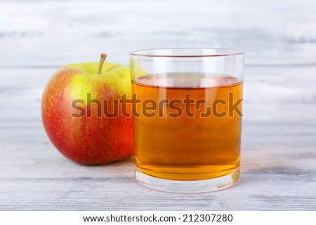 glass of apple juice and fresh apple on grey wooden table