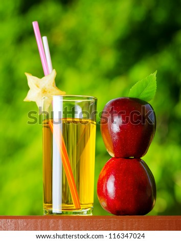 Glass of apple juice in a garden. - stock photo