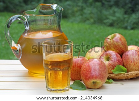Glass of apple juice with apples and pitcher in background - stock photo
