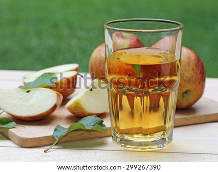 Glass of apple juice with apples and slices in background - stock photo