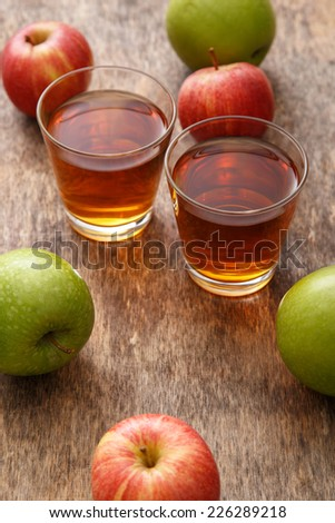 Glass of apple juice with apples on the table - stock photo