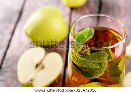 Glass of apple juice with fruits and fresh mint on table close up - stock photo