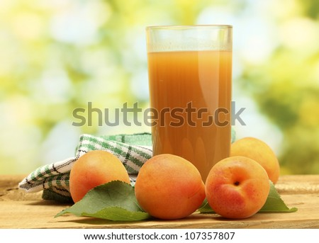 glass of apricot juice and fresh apricots on wooden table on green background