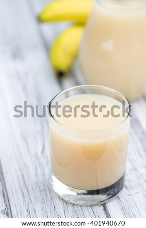 Glass of Banana Juice (close-up shot) on wooden background