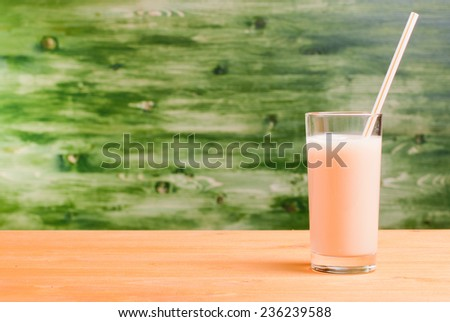 glass of banana juice on a yellow table on green background side view