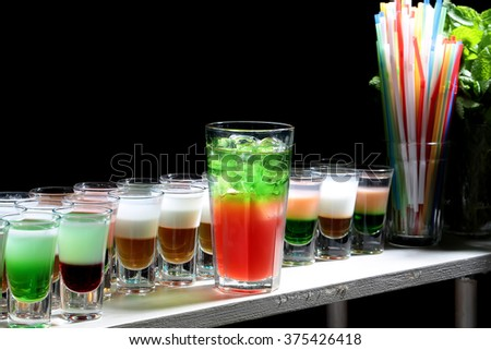 Glass of beautiful tasty sweet bright red green cocktail beverage with cold ice standing on bar near row of multicolored shots drinks and sipping straws closeup studio on black background, horizontal  - stock photo