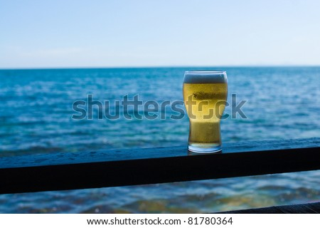 Glass of beer against sea