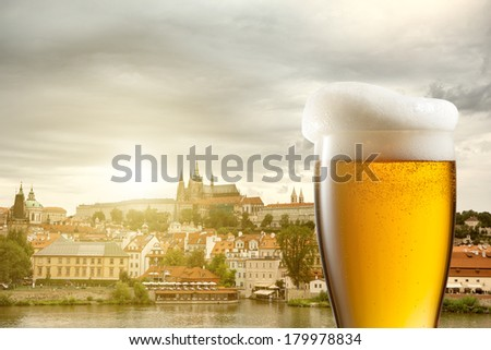 Glass of beer against view of the St. Vitus Cathedral in Prague - stock photo