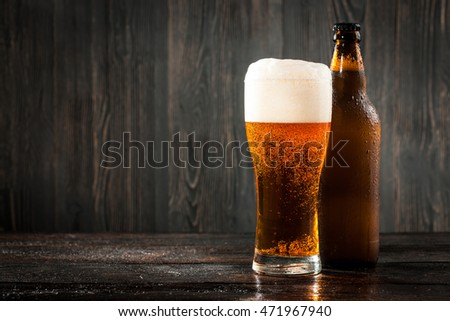 Glass of beer and beer bottle on wooden background