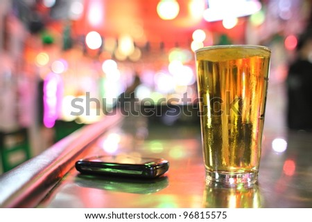 Glass of beer and cellphone at a bar.