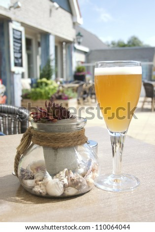 Glass of beer and decorative jug on a table in beach cafe
