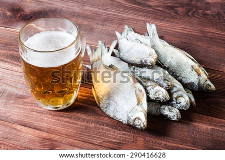 Glass of beer and dried fish, traditional russian snack. Wooden background. - stock photo