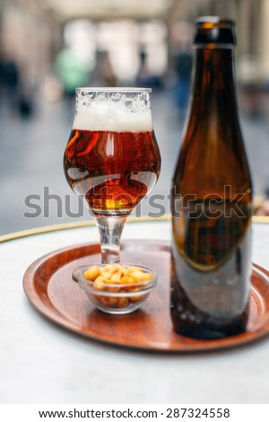 Glass of beer and empty bottle on the table