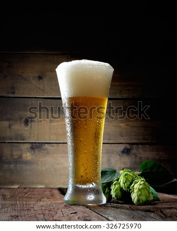 glass of beer and hop on a wooden background  - stock photo