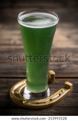 Glass of beer and horseshoe for St Patricks day - stock photo