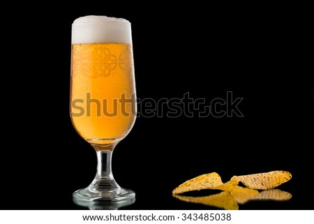 Glass of beer and nachos isolated on black background. Half of a pint