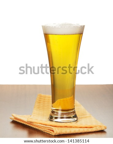 Glass of beer and napkin on a gray background