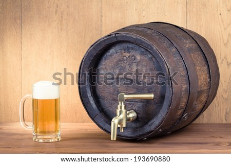 Glass of beer and old oak wood barrel