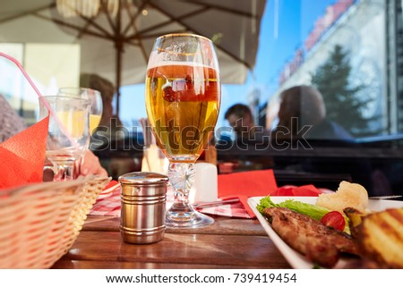 Glass of beer and street food on a cafe table.