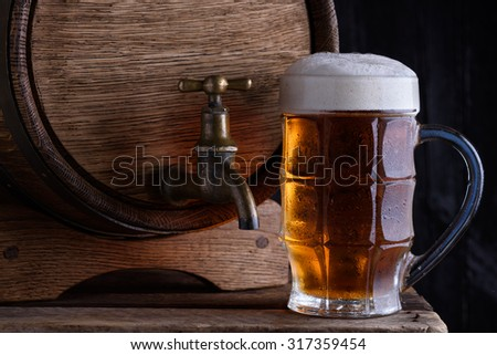Glass of beer and vintage beer barrel still life - stock photo