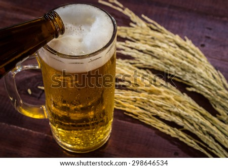 glass of beer and wheat on wooden table