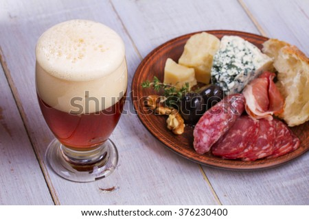 Glass of beer. Cheese,  prosciutto, salami, rosemary, nuts, olives and bread - stock photo
