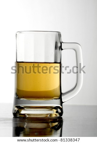 Glass of beer close-up on white background.