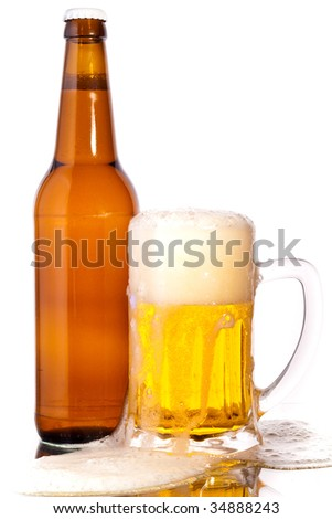 Glass of beer in the front with foam with bottle of beer in the back