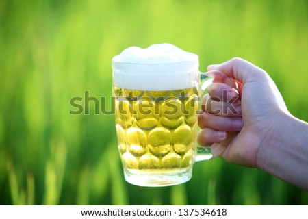 Glass of beer in the hand with green background. - stock photo