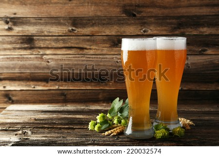 Glass of beer on a brown wooden background - stock photo