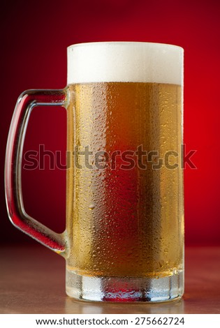 glass of beer on a stone table over a red background - stock photo