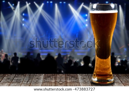 Glass of beer on a wooden background concert lights bokeh.Concept Festive Celebrations.