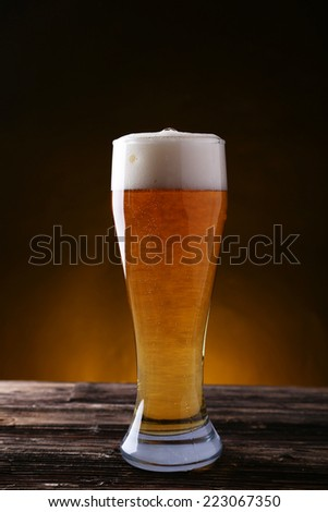 Glass of beer on brown wooden background