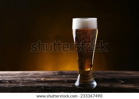 Glass of beer on brown wooden background - stock photo