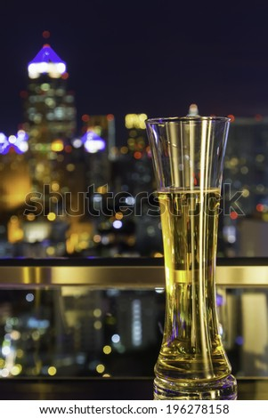Glass of beer on city background
